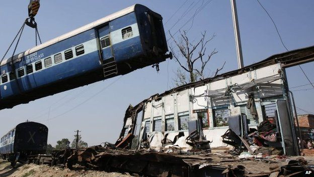 A train compartment is lifted by a crane as the mangled remains of another compartment stands at the site of an accident near Bachhrawan village in the northern Indian state of Uttar Pradesh, 20 March 2015.