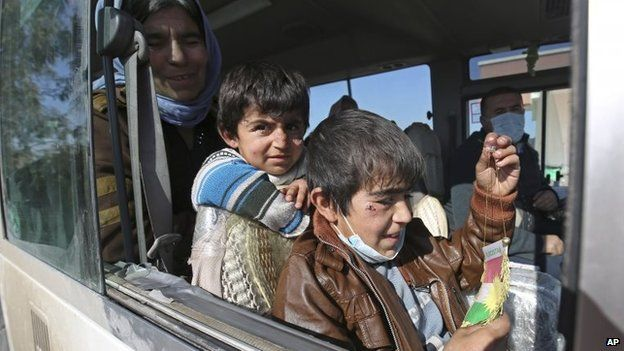 Two Yazidi boys, suffering from several infections from mosquito bites while held by Islamic State, wait with their mother inside a bus before being driven to the Kurdish city of Dohuk, in Alton Kupri, outside Kirkuk, Iraq, 18 January 2015