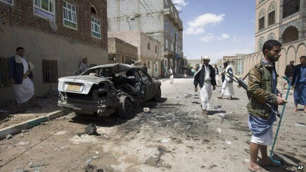Houthi rebels stand near a damaged car after a bomb attack in Sanaa, Yemen, 20 March 2015