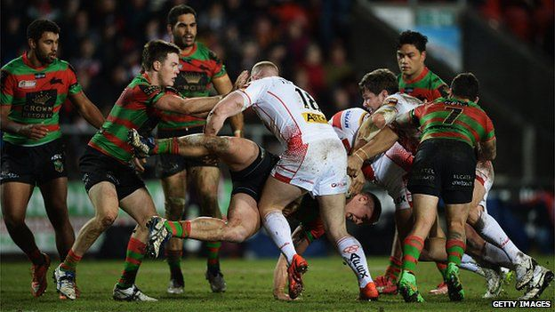 Jason Clark of South Sydney Rabbitohs is tackled by Luke Thompson of St Helens (18) during the World Club Challenge match between St Helens and South Sydney Rabbitohs at Langtree Park on 22 February 2015 in St Helens, England