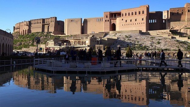 People walk on a pontoon at the bottom of the Erbil Citadel in the capital of the autonomous Kurdish region of northern Iraq