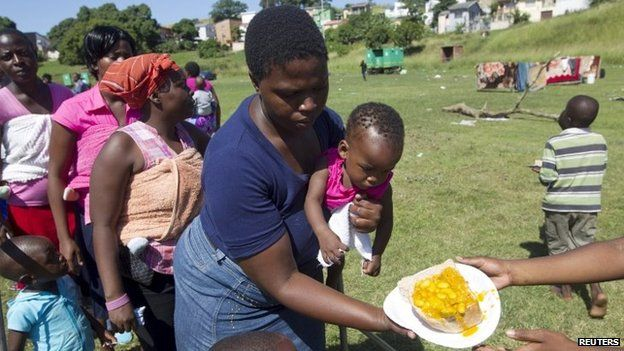 Women with children, who are the first to receive food, stand on a sports field in Chatsworth in the south of Durban