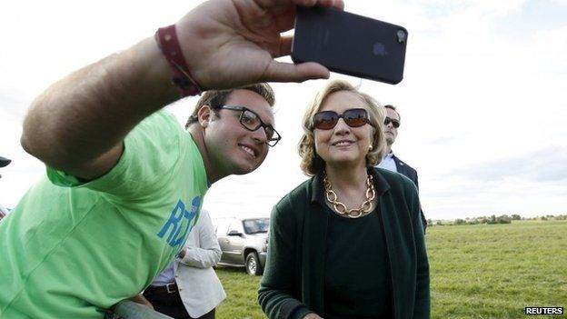 Former US Secretary of State Hillary Clinton poses for a photo with a supporter at the 37th Harkin Steak Fry in Indianola, Iowa in this 14 September 2014