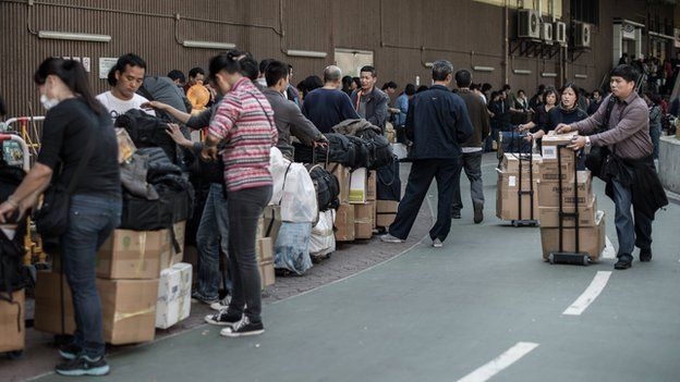 In this picture taken in Hong Kong on January 29, 2013, people arrive to queue up to get their packages weighed at the Sheung Shui train station prior to their journey back to mainland China.