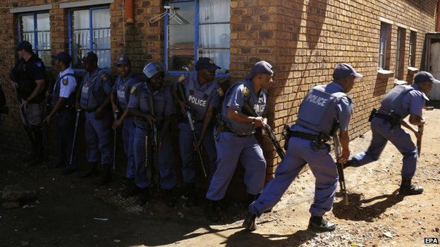Police officers advance to enter men's hostel after xenophobic violence in the area overnight forced foreign shop owners to close their shops for fear of attack in Actonville, Johannesburg on 16 April 2015