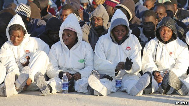 Migrants rest after they disembarked in the Sicilian harbour of Augusta, April 16, 2015