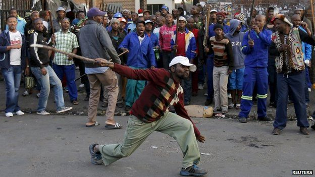 A local man gestures with a stick outside a hostel during the anti-immigrant violence in Johannesburg, April 17, 2015