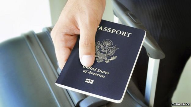 US passport and luggage in the hand of a traveller
