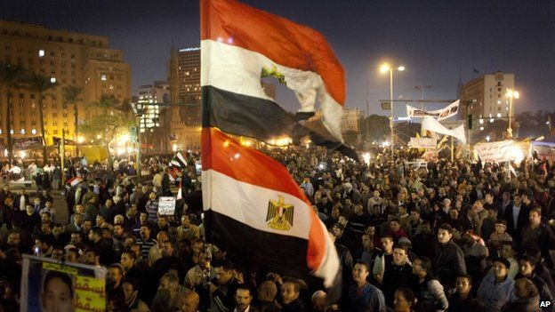 """Egyptians opposing president Mohammed Morsi fly their national flags as one holds a poster with a picture of a slain protester with Arabic that reads """"Martyr Mostafa Helmi, down with the rule of the Morshid,"""" during a rally in Tahrir Square, Cairo, Egypt, Tuesday, Dec. 18, 2012"""