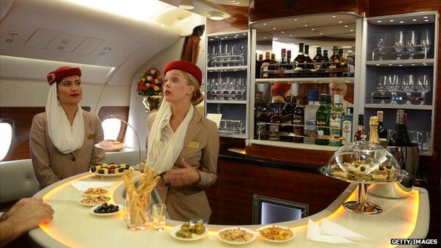 Flight attendants at the bar of the executive suite cabin of an Emirates Airbus A380