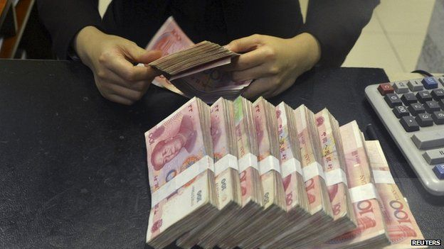 A clerk counts 100 Chinese yuan banknotes