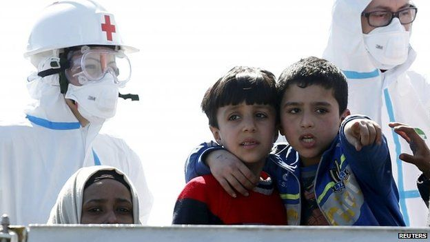 Children gesture on a ship landing on the Sicilian coast