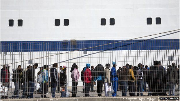 Migrant men wait to board a ship bound for Sicily in Lampedusa, Italy. 22 April 2015
