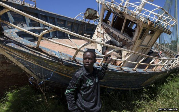 "A migrant from Nigeria stands in a ""boat graveyard"" 22 April 2015 in Lampedusa, Italy."