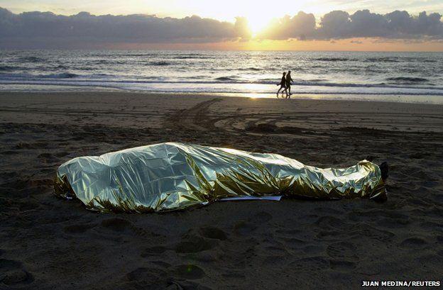 Fuerteventura, 2003 - a body lies on the beach as tourists go for a walk