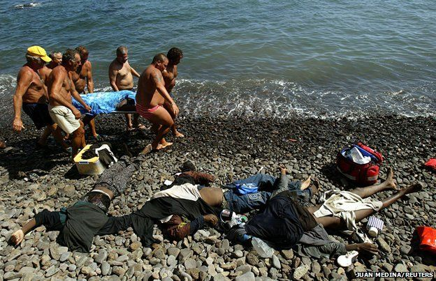 Spain, 2004 - rescuers pull a body out of the sea - several already lie on the beach