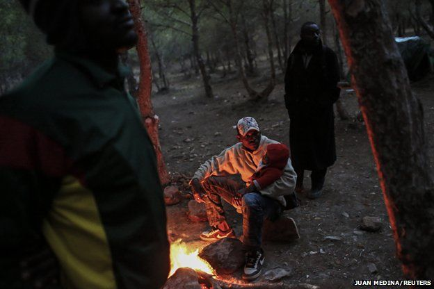 A migrant warms himself by a fire at a clandestine campsite in northern Morocco near the border fence with Spain's North African enclave Melilla, 2013