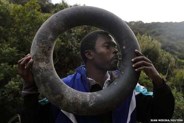 A migrant blows up an inner tyre