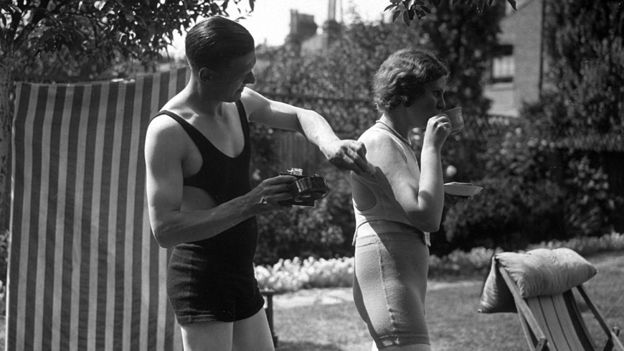 Man rubs suntan lotion on his wife's back, circa 1935