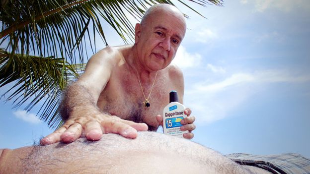 Applying sun cream on a beach in Florida, USA
