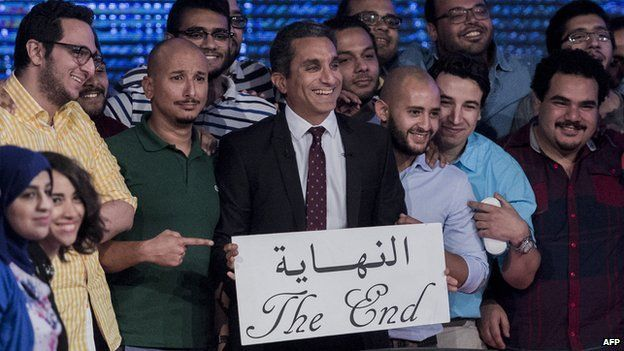 Egyptian satirist and television host Bassem Youssef (C) and his team hold a placard reading in Arabic 'the end' during a press conference to announce the end of his TV show 2 June 2014