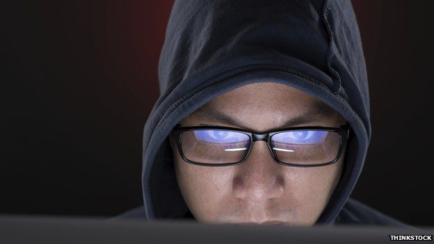 Shifty-looking man in front of computer screen