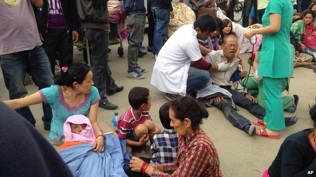 An injured man receives treatment outside the Medicare Hospital in Kathmandu, Nepal, Saturday, April 25, 2015