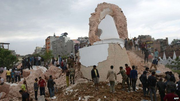 Nepalese rescue members and onlookers gather at the collapsed Dharahara Tower in Kathmandu on April 25, 2015