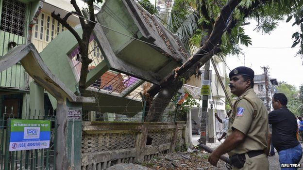 An Indian security personnel stands near a collapsed house after an earthquake in Siliguri, India