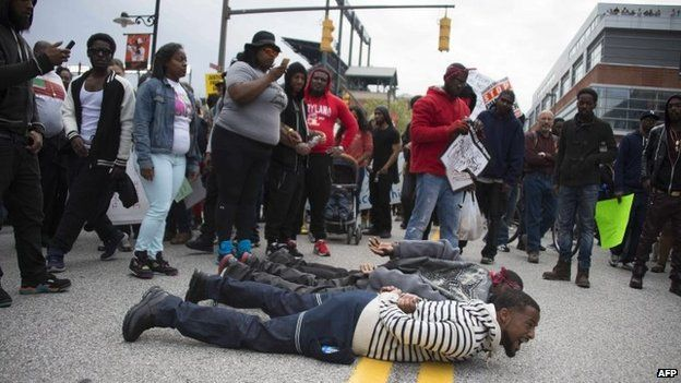 Demonstrators lie on the street to block traffic as others march protesting the death of Freddie Gray, an African American man who died of spinal cord injuries in police custody, in Baltimore, Maryland, on 25 April 2015