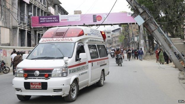 An ambulance drives next to a damaged power pylon after an earthquake caused serious damage in Kathmandu (25 April 2015)
