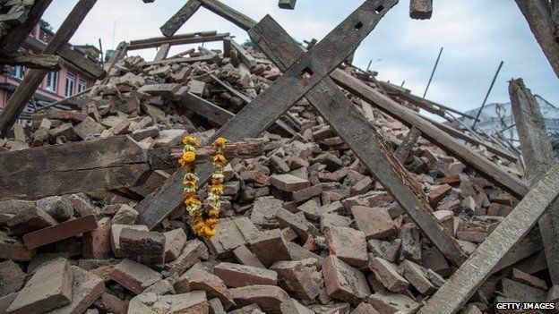 Flowers are left by survivors on top of debris from a collapsed building at Basantapur Durbar Square in Kathmandu (25 April 2015)