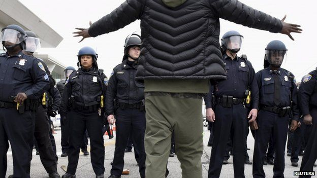 A demonstrator gestures towards a line of police near Camden Yards during a protest against the death in police custody of Freddie Gray in Baltimore April 25, 2015