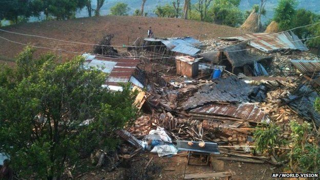 In this photo provided by World Vision, houses lie destroyed by Saturday's earthquake at Paslang village in Gorkha municipality, Nepal, Monday, April 27, 2015