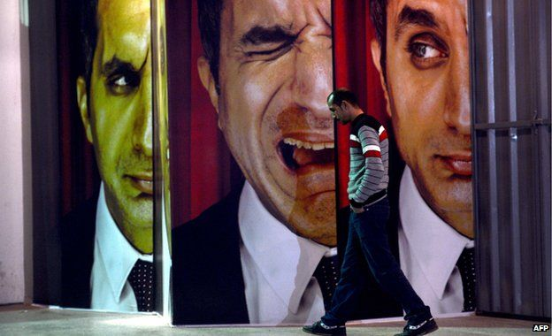 An Egyptian walks past posters of Egyptian satirist Bassem Youssef outside a theatre in Cairo 22 January 2013