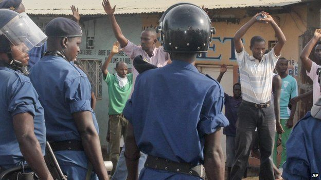 Opposition protesters and others hold their hands in the air when confronted by Burundian riot police in the capital Bujumbura, Burundi Monday, April 27, 2015