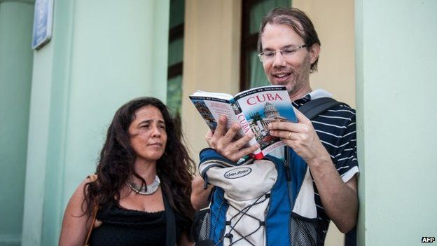 Tourists from the United States read a guide book on Cuba, in the streets of Havana on 6 April, 2015.