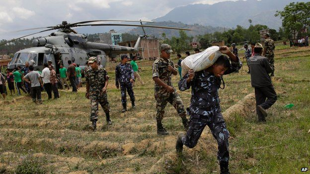 Nepalese soldiers unloading relief supplies from an Indian air force helicopter