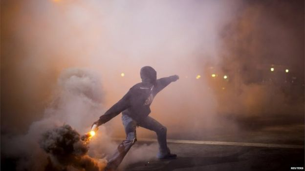 Protester throws gas canister at police