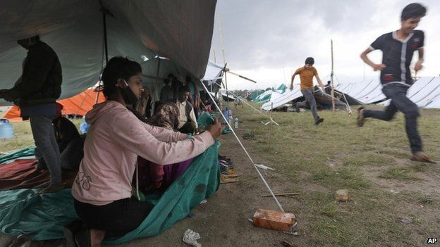 A Nepalese woman victim of an earthquake fixes her makeshift tent from a sudden rain in Kathmandu, Nepal, Tuesday, April 28, 2015.