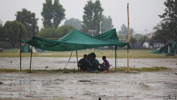 Earthquake victims sit under a makeshift shelter as it rains in Kathmandu (30 April 2015)
