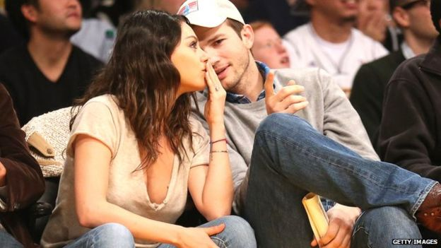 Ashton Kutcher has a private chat with his wife at a sports game