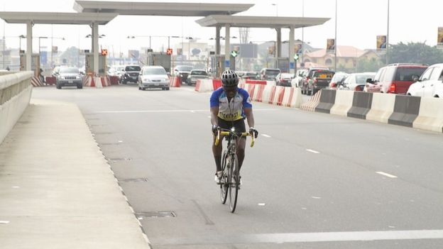A cyclist by a toll bridge in Lagos, Nigeria
