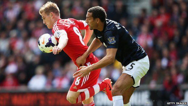 Steven Davis of Southampton holds off Rio Ferdinand
