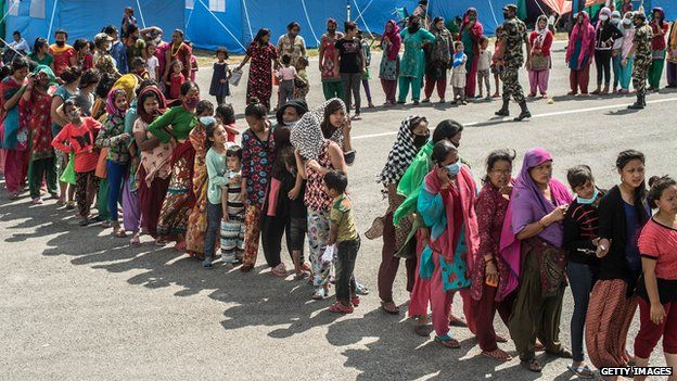 Victims of the earthquake queue to receive food and goods at a relief camp in Kathmandu