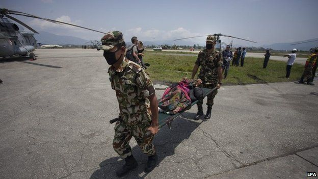 Nepali soldiers carry an injured woman rescued form Sindhupalchock district of Nepal, at Kathmandu International Airport