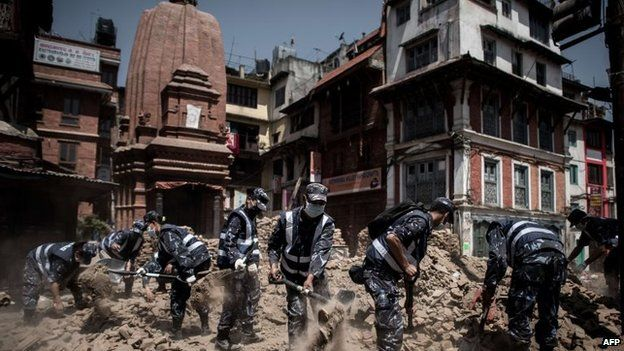 Members of the Nepalese police clear debris from the historical Durbar square in Kathmandu