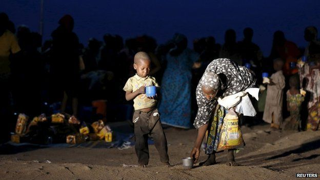 A child and mother rescued from Boko Haram in Sambisa forest by Nigeria Military pick up their food after arriving at the internally displaced people's camp in Yola, Adamawa State, Nigeria, 2 May 2015