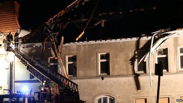 Firefighters inspect a damaged roof in Buetzow, Germany, 05 May 2015