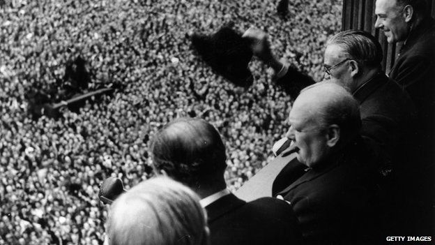 British Prime Minister Winston Churchill (1874 - 1965) waving to crowds gathered in Whitehall on VE Day, 8th May 1945.